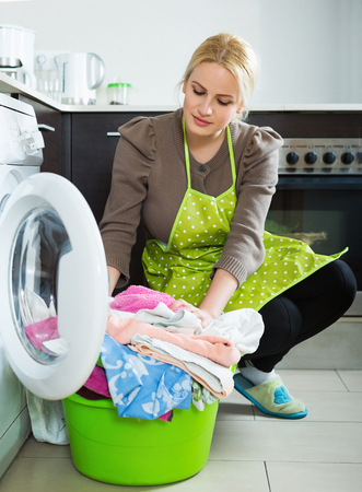 the weariness: Home laundry. Unhappy girl using washing machine at home Stock Photo