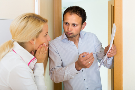 condemnation: Businessman trying to collect arrearages from housewife at doorway Stock Photo
