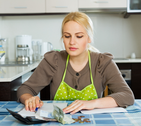 parsimony: Blond woman calculating the family budget at  home Stock Photo