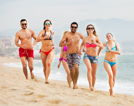 freetime: Happy people running at a beach