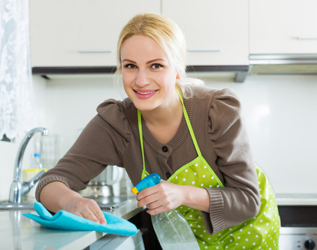 kitchen furniture: Happy blonde housewife cleaning furniture in kitchen