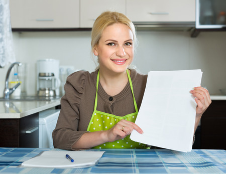 contractual: Happy girl sitting at kitchen and signing contractual agreement for renting new flat Stock Photo