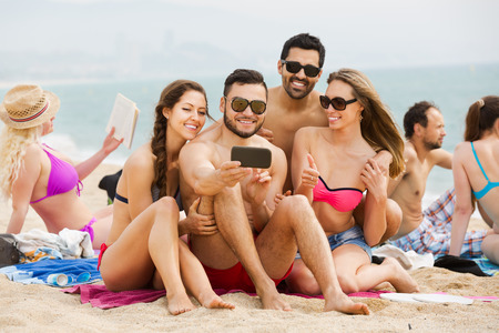 recollections: Cheerful adults posing and taking a pictures on a smartphone