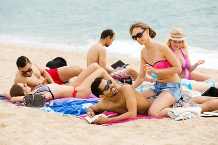 sunburn: Happy couple using cream for sunburn on the beach.Focus on couple