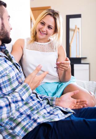 blabbing: Cheerful man and young woman friendly chatting at home Stock Photo