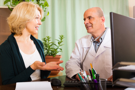 Mature  doctor talking with aged female patient in clinic