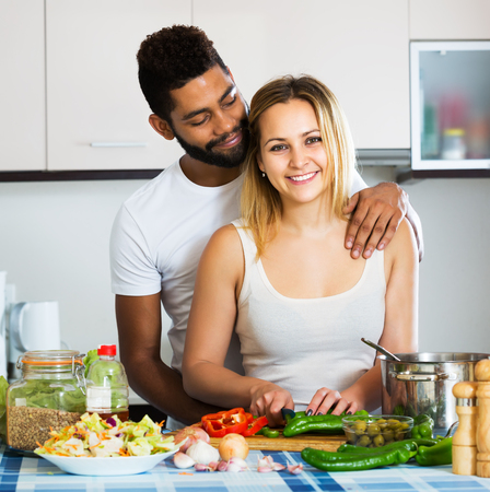 interracial couple: Young interracial couple cooking vegetables and laughing in the kitchen Stock Photo