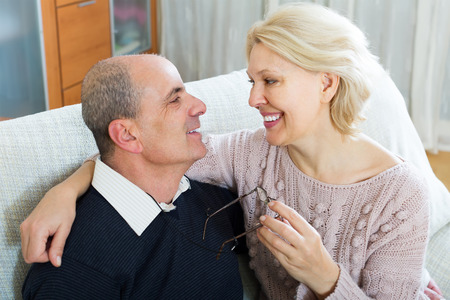 gladful: Happy senior loving husband and wife cuddling on couch at home Stock Photo