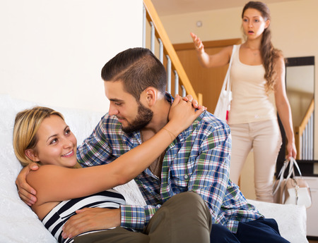 unfaithful: Sad jealous guest catching partner with embracing lover indoor