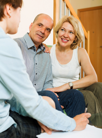 private insurance: Positive mature  couple discussing details of private insurance with friendly agent