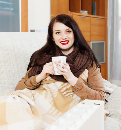 Happy woman  with cup near  electric heater Stock Photo
