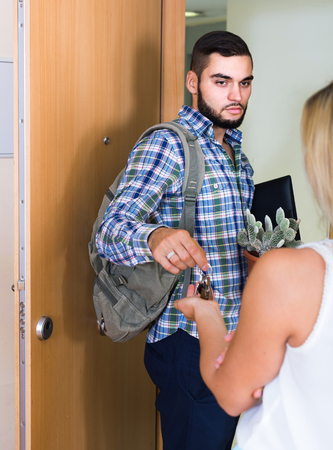 moving out: Upset european adult watching how spouse moving out with baggage Stock Photo
