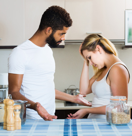 interracial family: Young european interracial family couple with serious faces quarrelling in kitchen Stock Photo