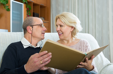 spouses: Portrait of loving senior smiling spouses with picture album indoors