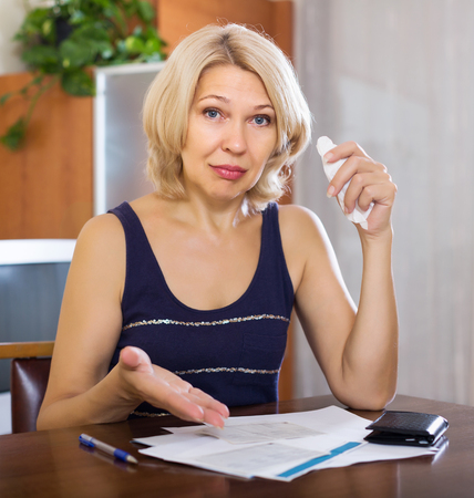 Serios mature blonde woman filling in financial documents at table in home interior