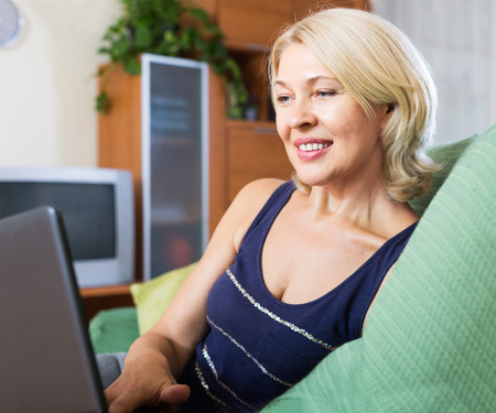 green sofa: smiling mature woman using laptop on green sofa in home Stock Photo