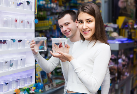 aquarian: Portrait of young couple selecting aquarium fish in display Stock Photo