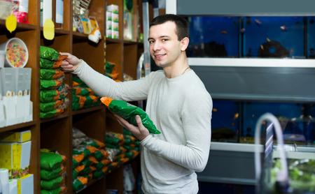 petshop: Portrait of happy american guy selecting vet food in petshop Stock Photo