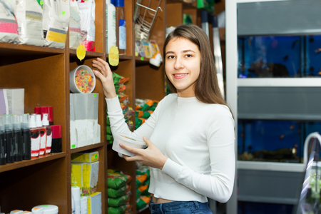 19's: Ordinary female customer choosing dry food for pets in petshop Stock Photo