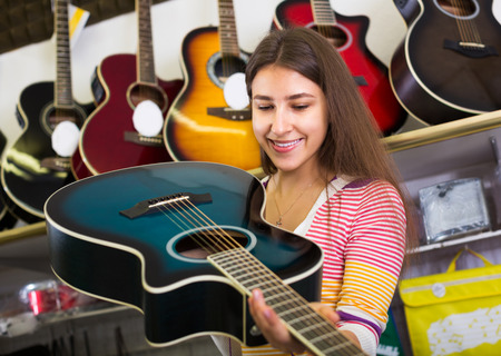 shopgirl: Portrait of young customer buying new guitar in store and smiling
