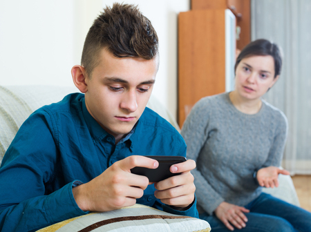 16s: Phubbing: tired mother asking for attention of teenager with cell phone