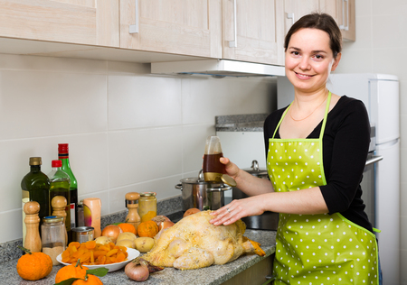 capon: Portrait of smiling young brunette in apron preparing capon at home kitchen Stock Photo