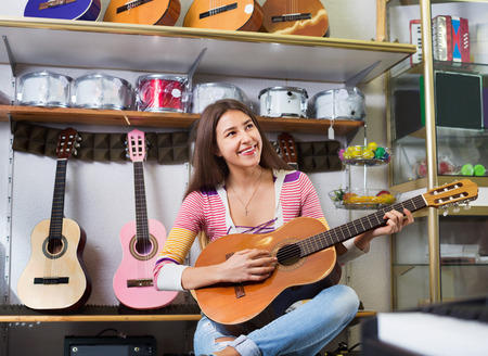 18's: Happy smiling teenage girl posing with classical guitar in shop