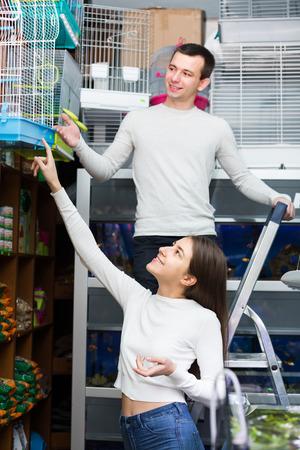 19's: girl and  boyfriend purchasing bird cage in petshop