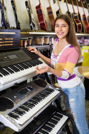 synthesiser: Smiling young girl selecting control keyboard for synthesiser in shop
