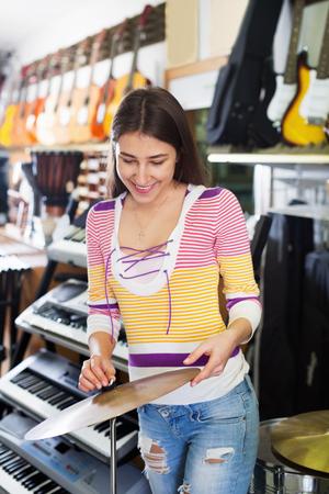 drum kit: Teenage girl shopping drum kit in music instruments studio