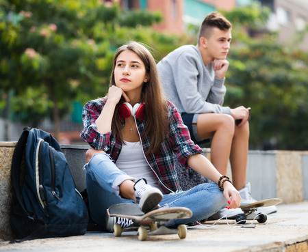 16s: Portrait of frustrated girl and angry boy teenagers after quarrel outdoors