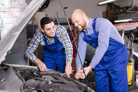 two car garage: Portrait of two happy professional car mechanics working together at garage Stock Photo