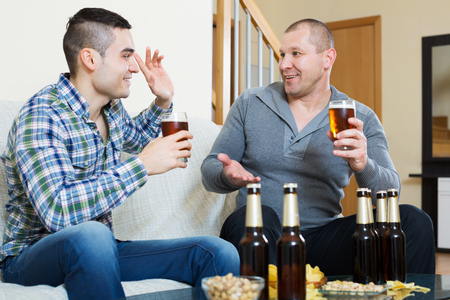 beer after work: Two colleagues sitting with beer after work indoor Stock Photo