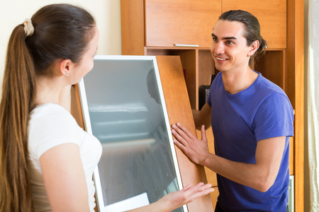 Happy smiling young couple moving furniture in room Stock Photo