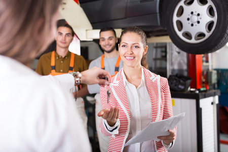 renewal: Insurance agent discussing with the mechanics renewal of car