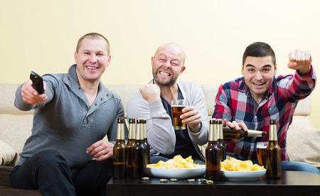 fandom: Three male friends sitting at table with beer and watching sport tv channel Stock Photo