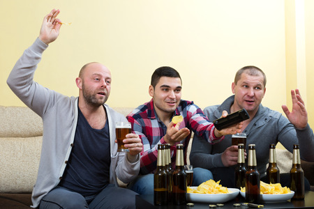 fandom: Three male friends sitting at table, drink beer and commenting sport tv channel Stock Photo