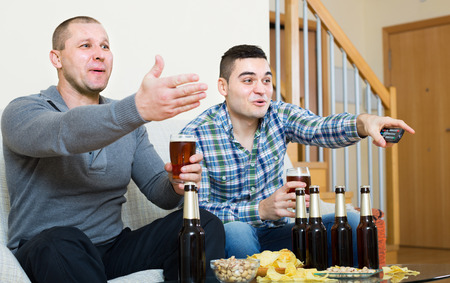 fandom: Two excited male friends drinking beer and watching football game indoor. Focus on one