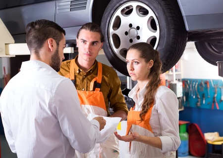 Unhappy client unsatisfied with the result of his car repairs is talking to a auto service crew with documents in his hand