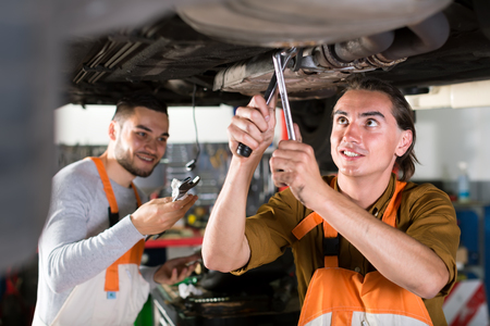 exhaust system: Positive workers at a car dealership are repairing a resonator in exhaust system of a lifted up car