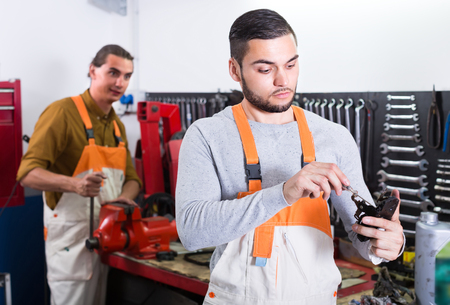 toiling: Two professional repairmen toiling in locksmiths workshop