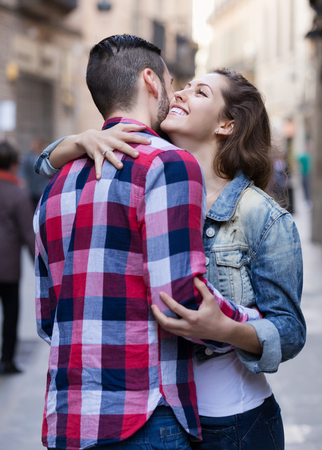 sidewalk talk: Happy young woman hugging her male friend outdoors