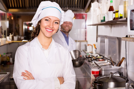 house robes: Young happy female cook cooking at professional kitchen in the take-away  restaurant