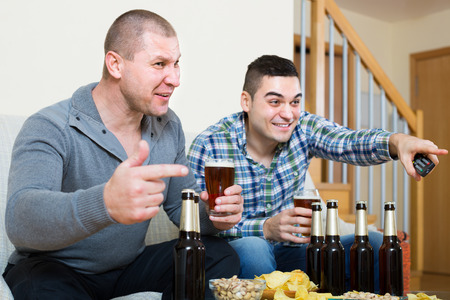 fandom: Two excited adult male friends drinking beer and watching football game at home. Focus on one