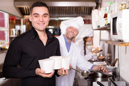 cook house: Portrait smiling client and cook buying take-away food at eating house Stock Photo