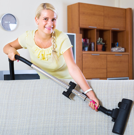 cleanup: positive woman using vacuum cleaner during regular clean-up