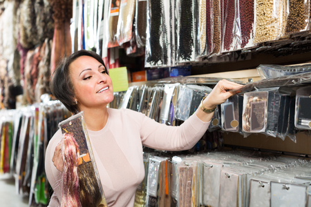chignon: Happy woman selecting different color hair extensions in shop