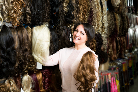Friendly female shop assistant selling natural hail ponytails, tresses and wigs