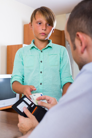 stingy: Middle aged father giving petty cash to teenage son Stock Photo