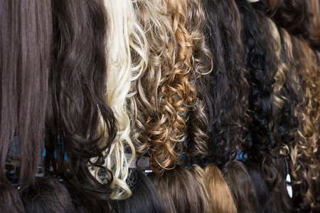 Different color blend clip-in hair extensions displayed in wig shop Stockfoto